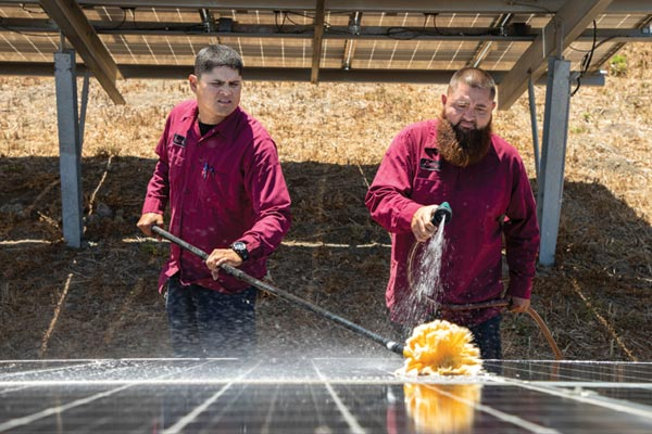 Gonzales City workers wash solar panels