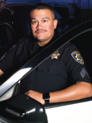 Seargeant Melgoza sitting in a squad car